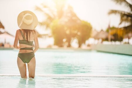 Woman relaxing by the pool in a luxury hotel resort enjoying perfect beach holiday vacation