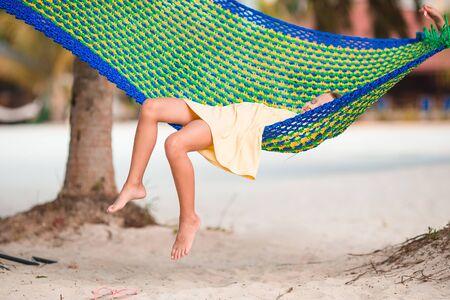 Beautiful little girl summer vacation relaxing in hammock