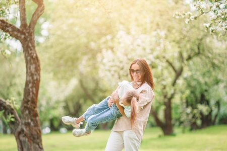 Family of mother and daughter in blooming cherry garden Banco de Imagens