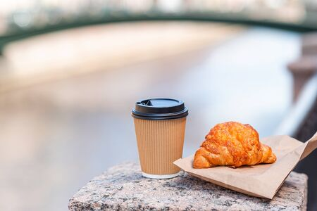 Traditional breakfast of coffee and fresh croissant outdoors