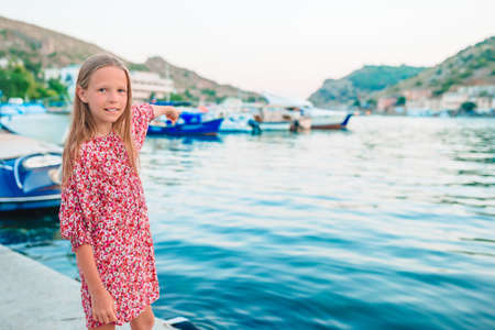 Adorable little girl in port at summer day Imagens
