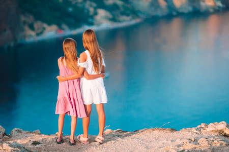 Children outdoor on edge of cliff seashore 免版税图像