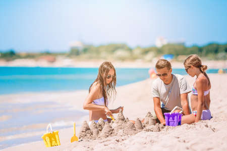 Father and kids making sand castle at tropical beach.