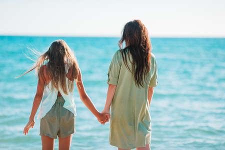 Beautiful mother and daughter on the beach enjoying summer vacation 版權商用圖片