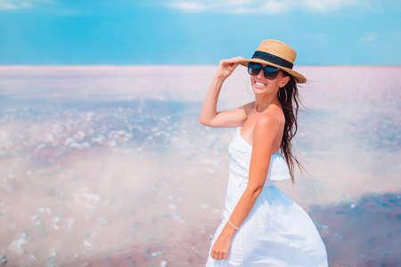 Woman in hat walk on a pink salt lake on a sunny summer day. 版權商用圖片