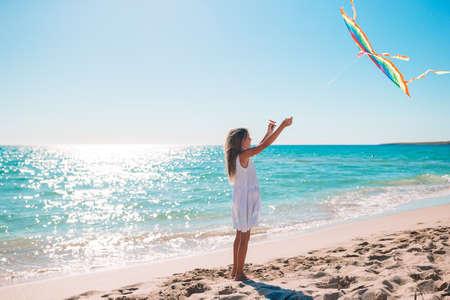 Little girl flying a kite on beach at sunset 版權商用圖片