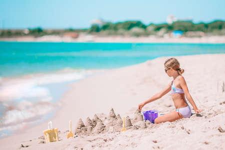 Little girl at tropical white beach making sand castle