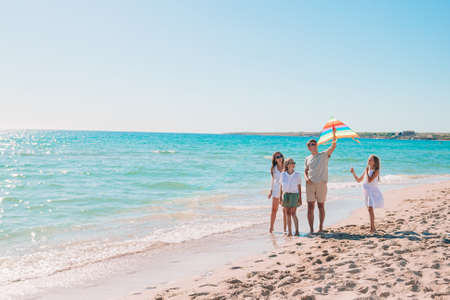 Happy young family with two kids with flying a kite on the beach 版權商用圖片