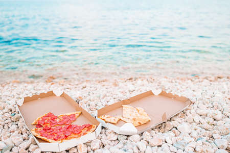Fresh pizza on the beach background of the sea