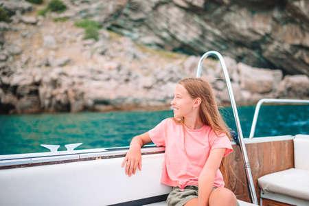 Little girl sailing on boat in clear open sea 版權商用圖片
