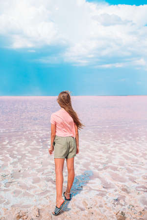Girl on a pink salt lake on a sunny summer day.