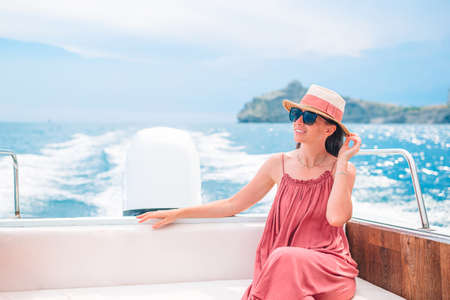 Woman in hat and dress sailing on boat in clear open sea 版權商用圖片