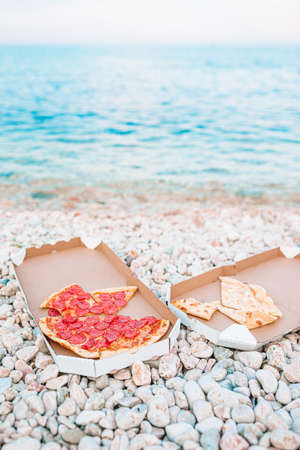 Fresh pizza on picnic on the beach background of the sea