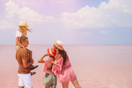 Family walk on a pink salt lake on a sunny summer day.