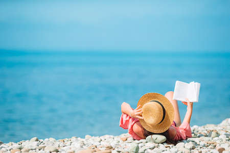 Young woman reading book during tropical white beach 版權商用圖片