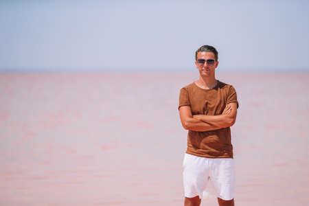 Tourist man walk on a pink salt lake on a sunny summer day.