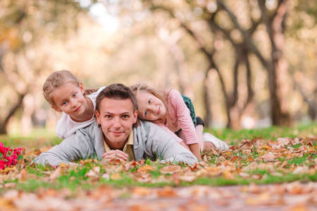 Family of dad and kids on beautiful autumn day in the park