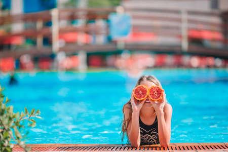 Little girl covering eyes with orange halves near eyes on background swimming pool