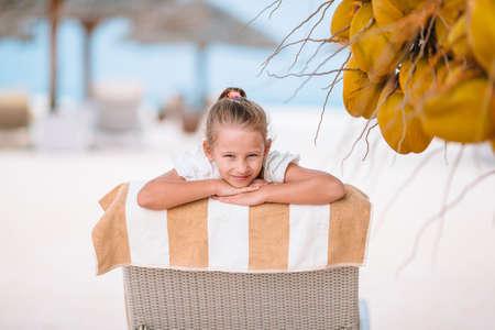 Little adorable girl near coconut on white tropical beach 版權商用圖片