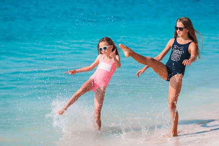 Little happy funny girls have a lot of fun at tropical beach playing together.