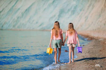 Adorable little girls having fun on the beach 免版税图像