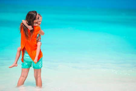 Beautiful mother and daughter at Caribbean beach enjoying summer vacation. 免版税图像