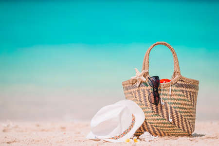 Beach accessories - straw bag, hat and unglasses on the beach