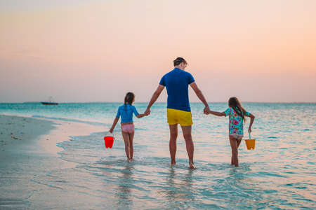 Happy father and his adorable little daughters at tropical beach having fun