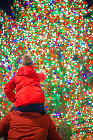 Happy girl with dad on the background of the Rockefeller Christmas tree in New York