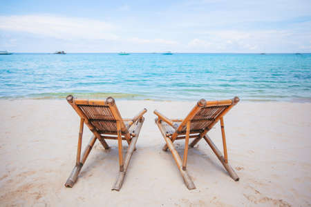 White lounge chairs on a beautiful tropical beach at Maldives Stock fotó
