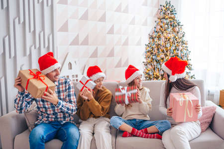 Happy young family with kids holding christmas presents