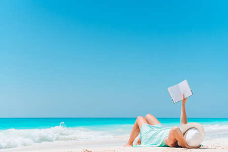 Young woman reading book during tropical white beach Stock fotó
