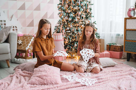 Adorable little girls sitting near the tree and making paper snow-flakes. Room decorated. Stock fotó