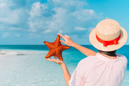 Adorable girl with starfish on the beach Stock fotó