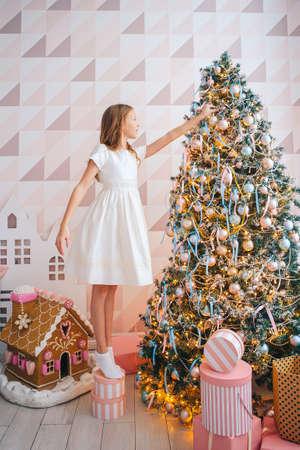 Beautiful girl near Christmas tree decorating Stock fotó