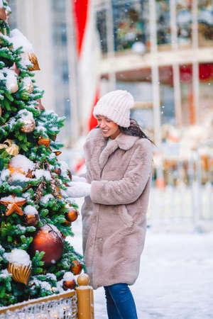 Happy girl near fir-tree branch in snow for new year. Stock fotó