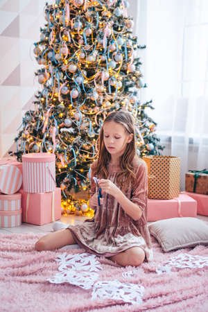 Adorable little girl sitting near the tree and making paper snow-flakes. Room decorated. Stock fotó