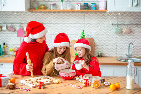 Happy family mother and daughters bake cookies for Christmas Stock fotó
