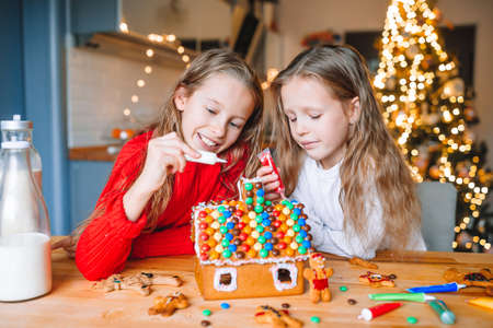 Little girls making Christmas gingerbread house in the kitchen Stock fotó
