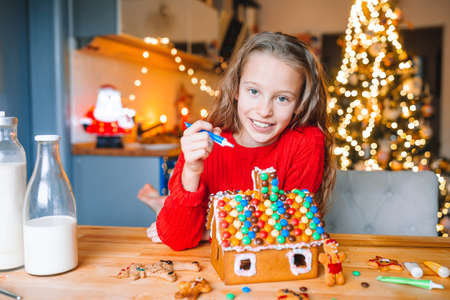 Little girl making Christmas gingerbread house in the kitchen