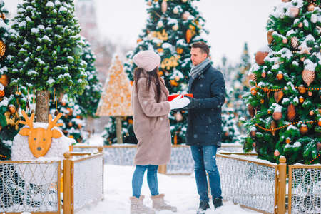 Young beautiful cheerful couple celebrating Christmas in the city street