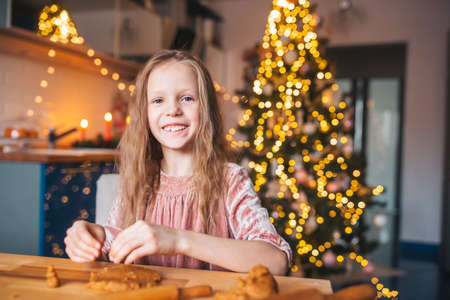 Adorable little girl baking Christmas gingerbread cookies Stock fotó