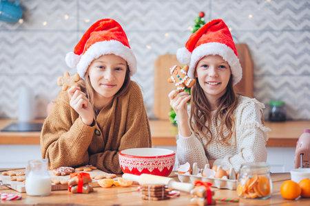 Little girls preparing Christmas gingerbread at home