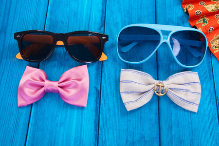 fan with red bow tie and sunglasses on blue wooden background photo