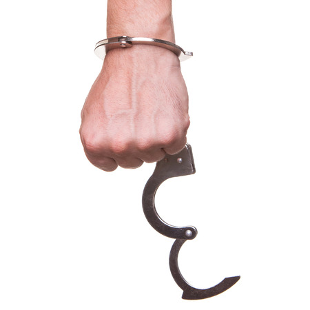 wristlets: male hand in police handcuffs showing gesture isolated on white background
