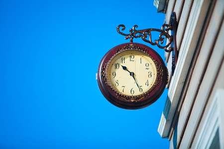 Street clock on the background of blue sky photo