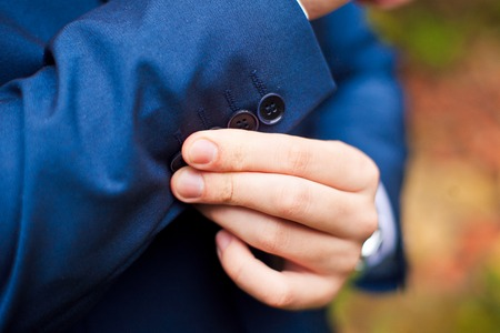 cuffs: Bridegroom wearing blue wedding suit and buttoning cuffs