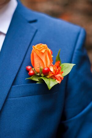 boutonniere of orange roses and red berries in the pocket of his jacket male