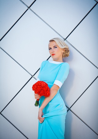 daring: Daring blonde rebel with brightly painted lips. In a long blue dress with bouquet of red in hand. Against the background of the rectangular decorative walls