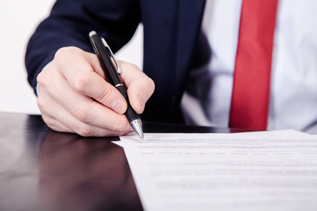 Business man signing a contract. A hand holding a fountain pen and about to sign a letter. Styling and small amount of grain applied. Stock Photo